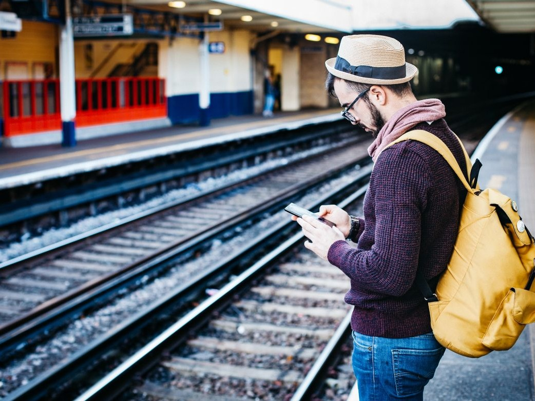 Man checking his phone at the train station, Planify, Group Travel Itinerary Solution